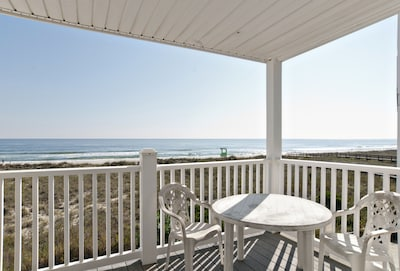 Private covered oceanfront deck off living room with outdoor seating.