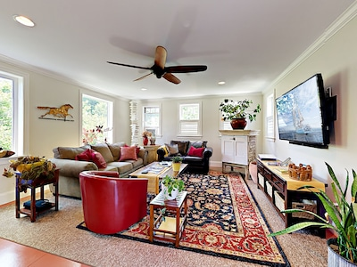 Living Area - A sofa, love seat, and a red leather chair offer comfortable and spacious seating in the living room