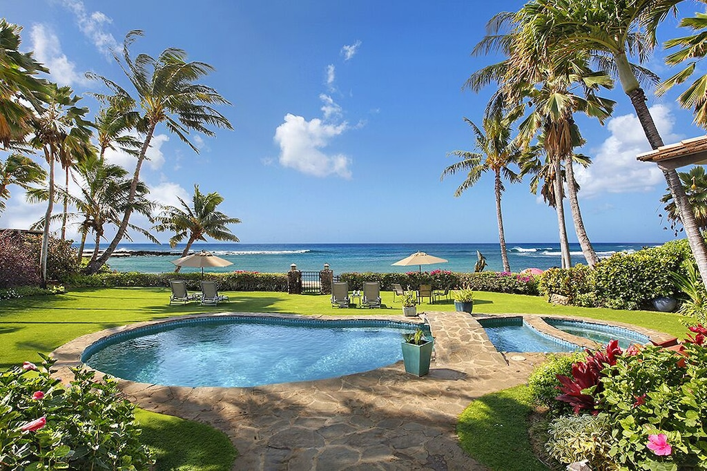 Pool and ocean views from a tropical garden in a Hawaiian vacation rental