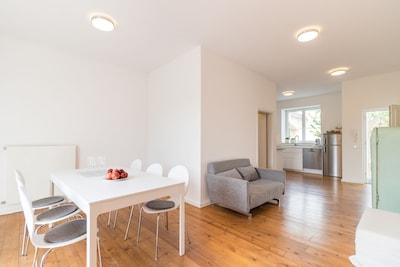 Stilvoll, edel, schlicht und hell: Wohn-Essbereich mit moderner, offener Küche.