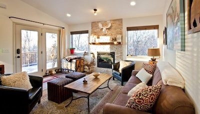 Living room with view of gas fireplace and entry with outside deck