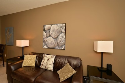 Living room has a leather couch and original art