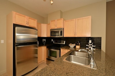 Kitchen has granite countertops and all the cooking equipment you need
