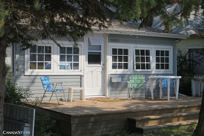 FRONT OF COTTAGE (faces 44th street)  Door opens into living room and dining area ( wooden table and chairs).