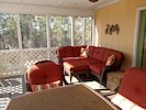 SCREENED PORCH SEATING AREA WITH VIEW OF GULF