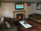"""Living room w/ 50"""" cable TV and marble outline fireplace"""