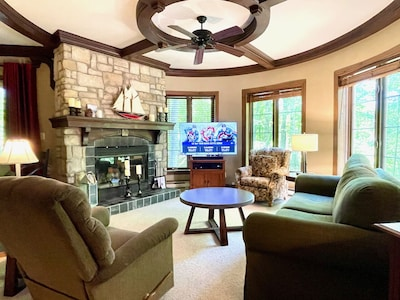 Spacious turret-style living room with stone fireplace