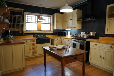 Fully equipped kitchen with custom cabinets, soapstone sink and gas range