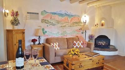 Sitting room with ceiling vigas, original hardwood floors; view towards mountain