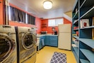 Kitchenette with open shelving, laundry, and a very groovy yellow floor!
