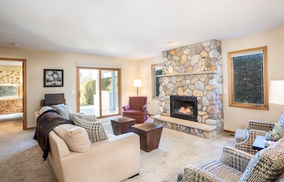 Open concept large living room with gas fireplace and views of Lake Leelanau