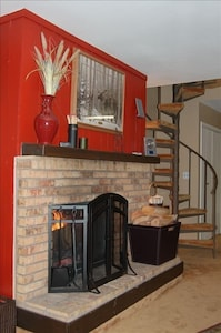 Wood burning fireplace and quaint spiral staircase to loft.