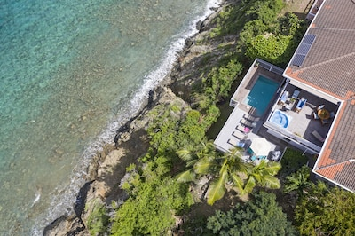 Drone view of private pool and hot tub and ocean beyond.  On the water!