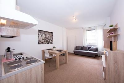 Wohnzimmer mit offener Küche und Schlafsofa für 2