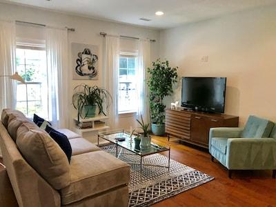 Modern living room, large screen TV, WIFI, hardwood floor, open tokitchen area.