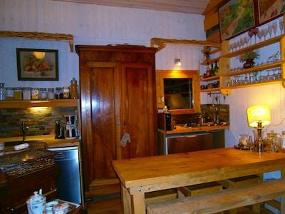 A gauche de l'armoire de rangement, coin- vaisselle, à droite, coin-cuisine.