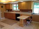 Kitchen sink, dishwasher, dish cabinets, built-in eating area.