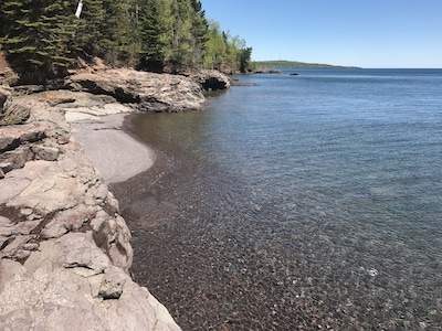 A sandy cove and shoreline ledgerock offer discovery and sanctuary for guests.