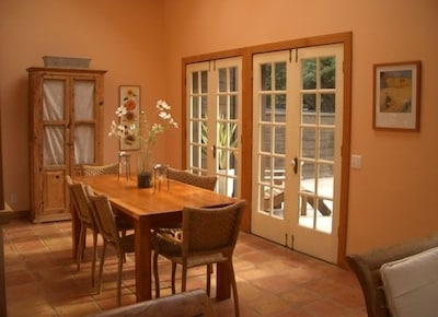Dining area looks out French doors into the garden