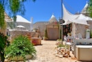 main trullo patio front with sun shade seating area with firepit