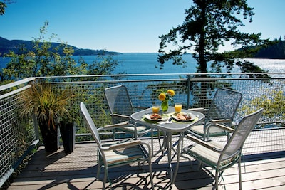 Sunny south facing waterfront deck w/ patio dining, briquette BBQ, beach access