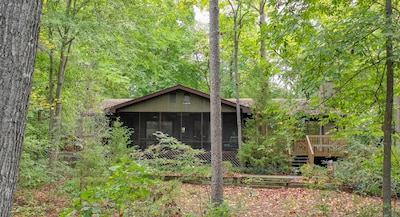 Nestled in the woods - view from lake to house. Deck on left of screen porch.