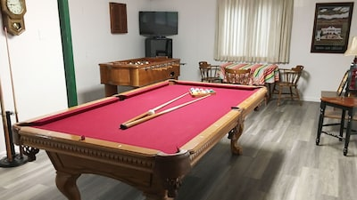 Game room with pool table, fooseball, darts and TV.