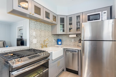 Custom kitchen. Gas stove, apron sink, quartz counters, Keurig coffee bar