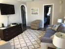 Living room with brand new flooring, large screen TV, queen size sleep sofa