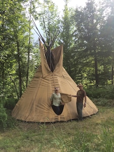 Traditional tipi surrounded by forest