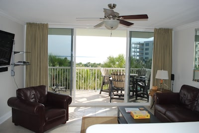 Enjoy the beautiful view of the bay and lazy river pool area from the balcony