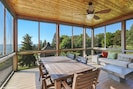 Expansive screened in porch with dining table and sectional sofa and lake views
