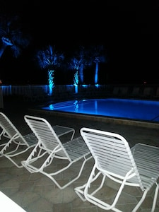 Pool at nighttime with beautiful blue lights around all landscaping