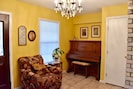 bright front room with antique piano!