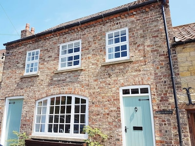 The stunning Coach House,  side walkway to garden and storage through left door.