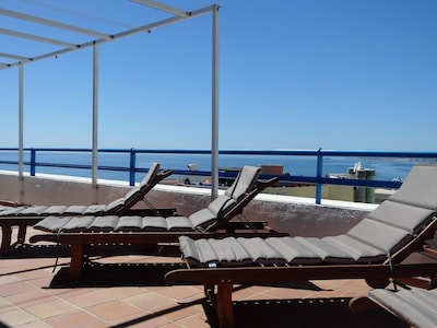 sunloungers on the terrace with retractable awnings for shade in summer