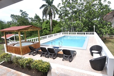 Swimming pool with Jacuzzi also BBQ pit on the ground to the left of the pool