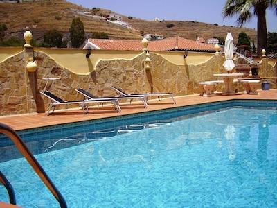 Pool mit Sonnenliegen und Grillecke
