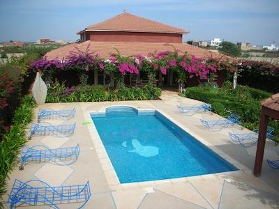 venez vous reposer au bord de la piscine au milieu d'un jardin fleuri et coloré