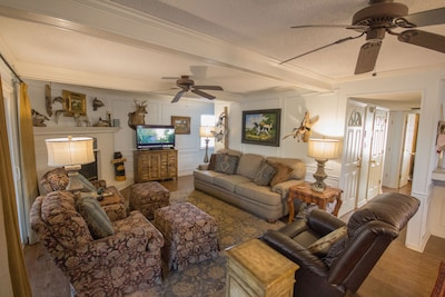 Family room with large sofa, two chairs with ottomans and a lazy boy recliner