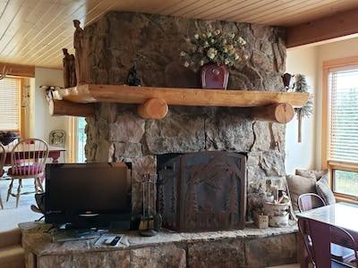 Wood burning fireplace in Living Room. TV to left of fireplace screen