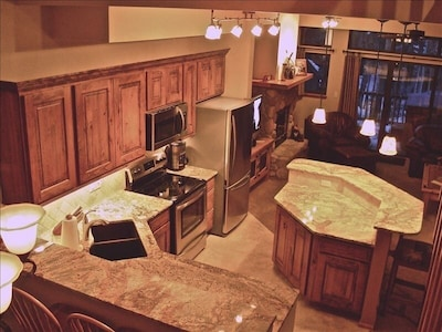 Birdseye view of fully equipped kitchen with living area in the background.