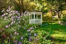 Sit and swing peacefully in the gazebo by the stream in the soft sunlit garden.