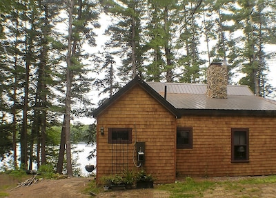 Back of cabin w/new shingles, roof and stone chimney