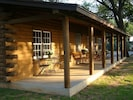 Front porch facing lake with table & chairs, porch swing,  & four rocking chairs