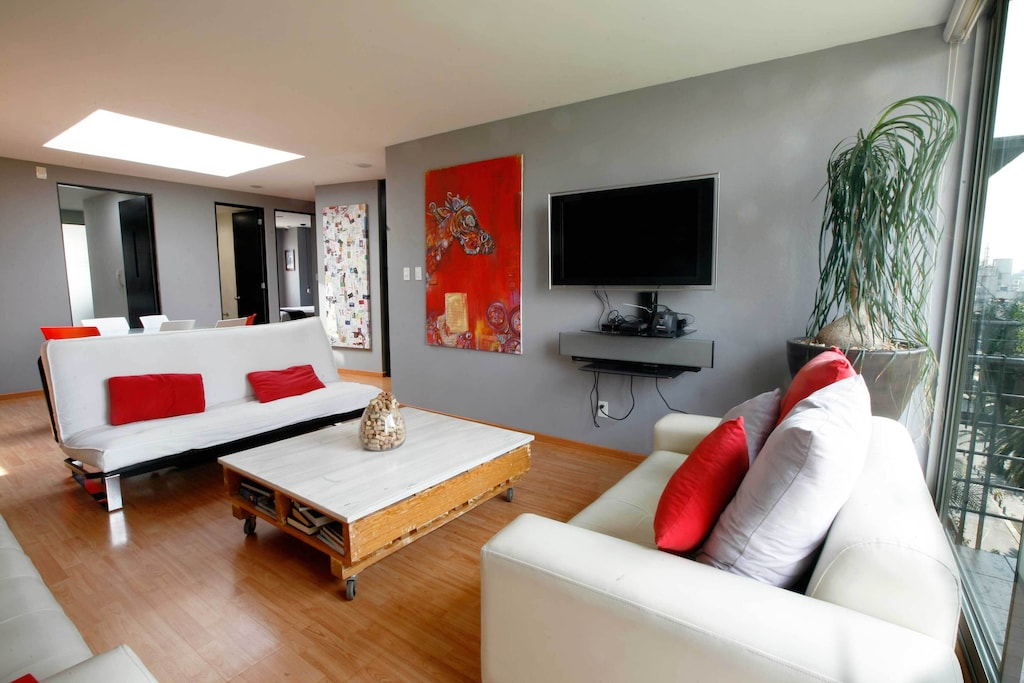 VRBO Mexico City: Living room with large plant, 2 sofas, large TV and modern decor