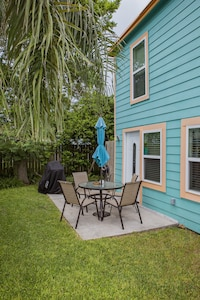 Small private yard with patio with table, chairs, shade umbrella.