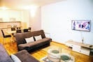 spacious living room with TV, air conditioning and balcony access