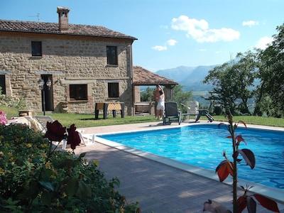 foto d'insieme della villa con piscina in un pomeriggio soleggiato..