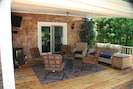 By Day/Poolside: Covered outdoor fire pit sitting area with fridge & LCD TV